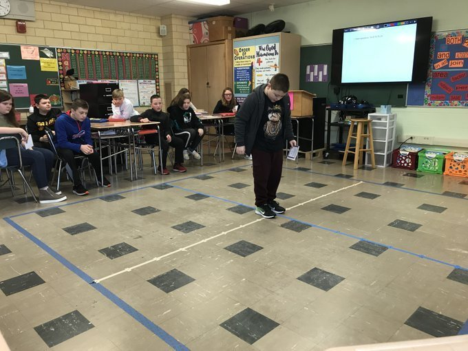 "Student ""plots"" himself on the classroom floor for coordinate grid learning activity"