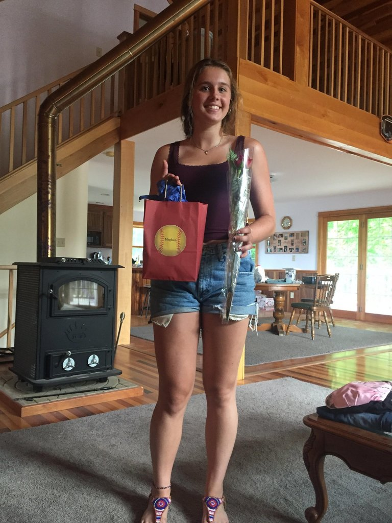 Softball player posing with her gifts